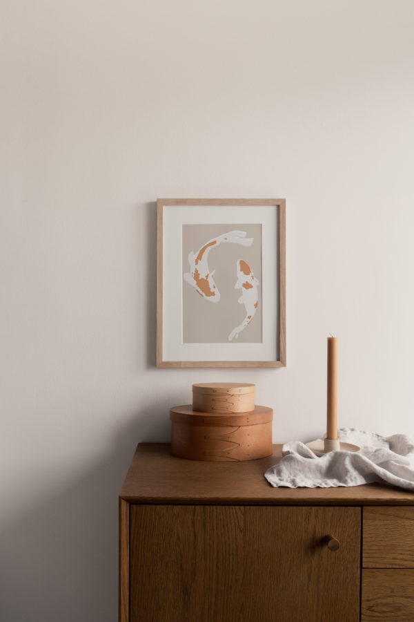 A styled shot of a framed japanese koi print on the wall above a walnut sideboard with natural accessories.
