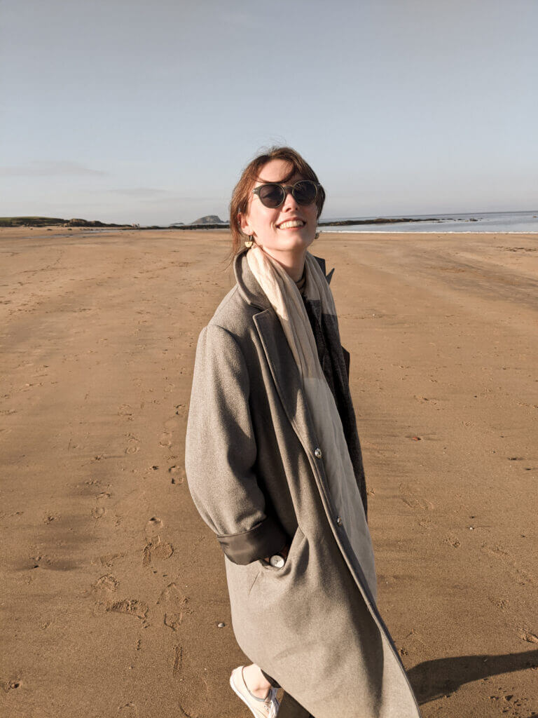 A photograph of me on north berwick beach. Wearing a long, grey wool coat and sunglasses, smiling at the camera.